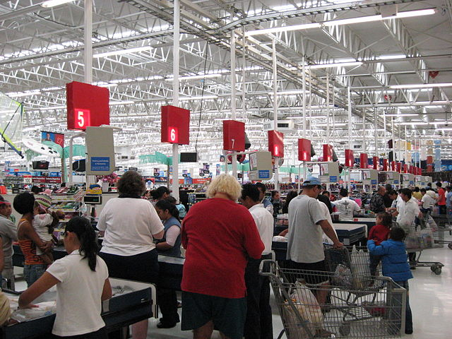 Checkouts_By_Bill_McChesney_from_USA_(8199_Playa_Del_Carmen_WalMart)__[CC-BY-SA-2.0_(http_creativecommons.org_licenses_by-sa_2.0)]_via_Wikimedia_Common